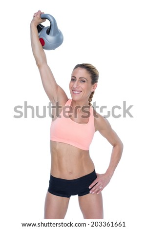 Female blonde lifting kettlebell above head smiling at camera on white background