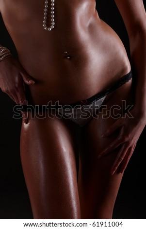 Female body in underwear over black background - stock photo