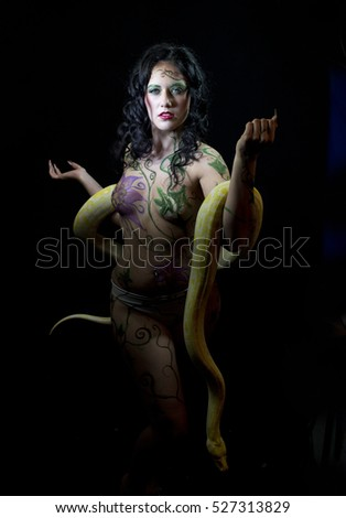 Female body painted  Eve with Burmese Python snake against black background