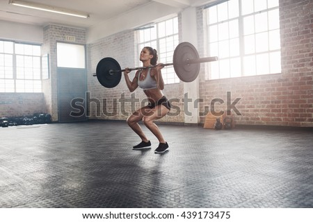 Female bodybuilder doing exercise with a heavy weight bar in gym. Full length shot of fitness woman practicing weightlifting at health club. - stock photo