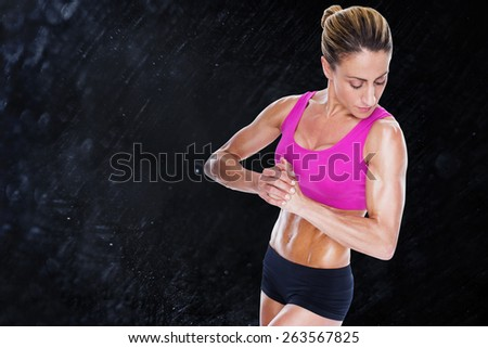 Female bodybuilder flexing with hands together against black background - stock photo