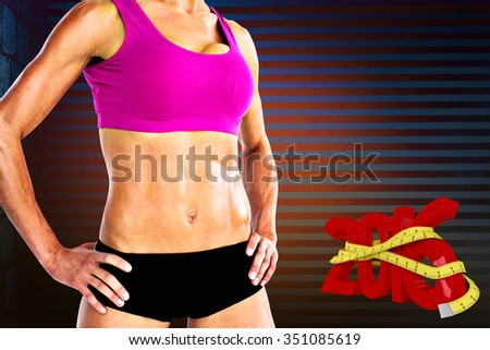 Female bodybuilder posing with hands on hips mid section against dark grey room - stock photo