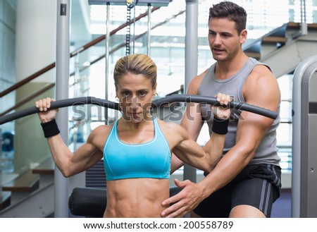 Female bodybuilder using weight machine for arms with encouraging trainer at the gym - stock photo