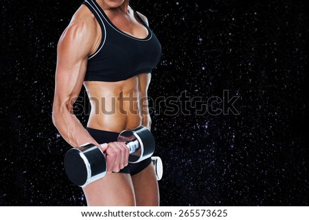 Female bodybuilder working out with large dumbbells mid section against black background - stock photo