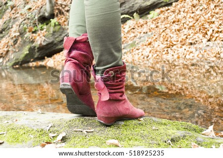 Female boots through a stream in the autumn