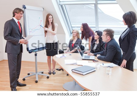 female boss is showing the statistics on the flipchart - stock photo