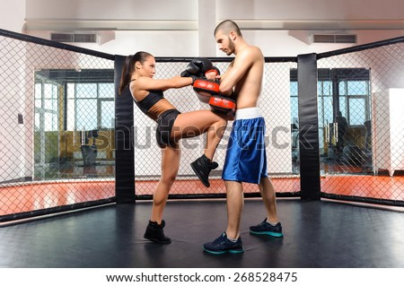 Female box. Training session of a female fighter kicking a punching pad held by a couch - stock photo