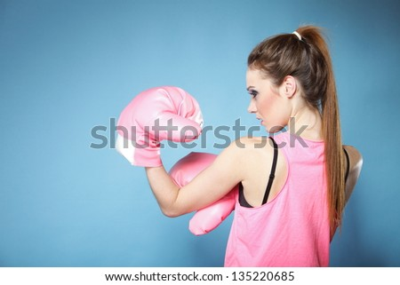Female boxer model wearing big fun pink gloves playing sports boxing studio shot, blue background - stock photo