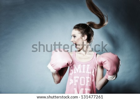 Female boxer model with big fun pink gloves playing sports boxing hair motion blue background - stock photo