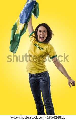 Female brazilian fan celebrating on a yellow background.