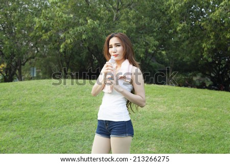 Female breaks standing and holding a bottle of water. On the grass in the public park. While jogging