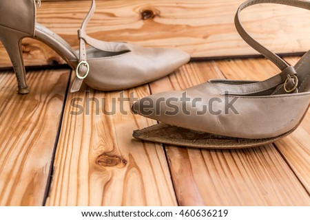 Female broken high heel shoes on wood background
