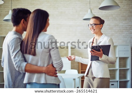 Female broker consulting young couple in realtor office - stock photo