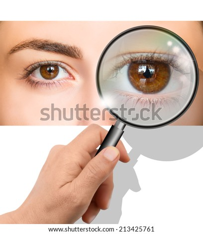 Female brown eye looking through magnifying glass  - stock photo