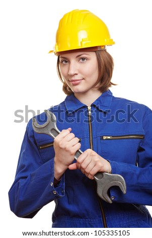 Female builder in overall with helmet and big wrench - stock photo