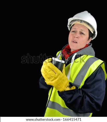 female builder, thinking, standing holding mug. Isolated image on black background. - stock photo