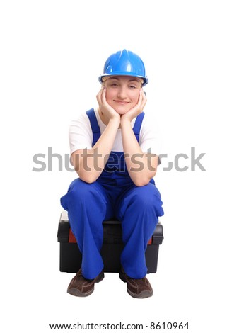 Female builder wearing blue helmet and jumpsuit sitting on toolbox with head resting on her hands over white