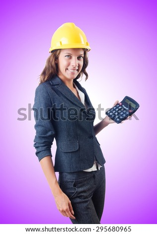 Female builder with calculator against gradient