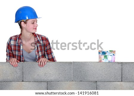 Female builder with money - stock photo