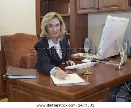 female business executive offers a pen to sign document - stock photo