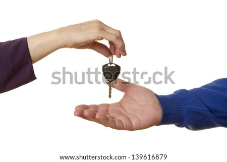 Female business person handing over car keys to a casual senior caucasian man, isolated on white. - stock photo
