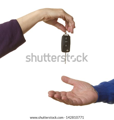 Female business person handing over car keys to a casual senior caucasian man, isolated on white.