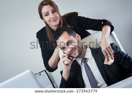 Female business woman giving money to businessman. Putting money him in the pocket while he is talking on the phone. - stock photo