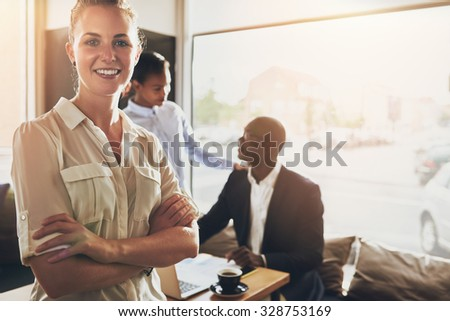 Female business woman, standing in front of colleagues in small office space - stock photo