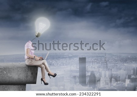 Female businessperson with balloon head sitting on roof while using laptop, symbolizing creative businesswoman - stock photo