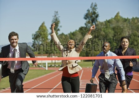 Female businesswoman cheering with competitors running on the racing track - stock photo