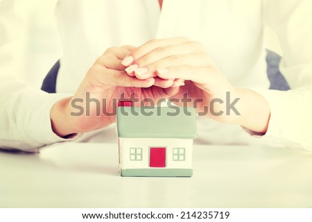 Female businesswoman hands protecting house. Home protecting concept for insurance or security - stock photo