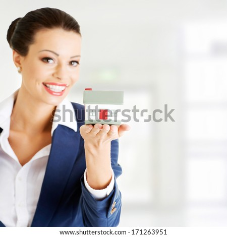 Female businesswoman holding and protecting house. Home protecting concept for insurance or security or real estate - stock photo