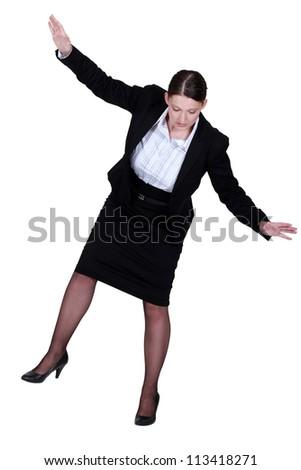 female businesswoman miming tightrope walker - stock photo