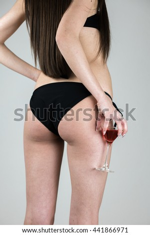 Female buttocks of young woman in panties with red cocktail in a Martini glass. Sexy girl in bikini with Cosmopolitan cocktail. - stock photo