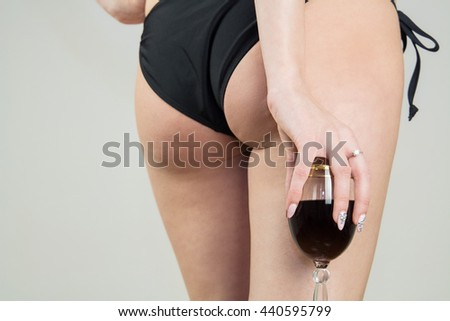 Female buttocks of young woman in panties with red wine in a glass. Sexy girl in bikini with red wine. - stock photo