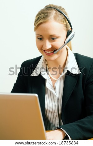 Female call center operator in front of a computer doing customer care work - stock photo