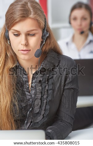 Female call center service operator at work. Portrait of pretty girl with headset at workplace. Effective and efficient business information, help and support concept - stock photo