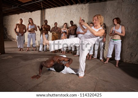 Female capoeria performer throws a kick at partner during practice - stock photo