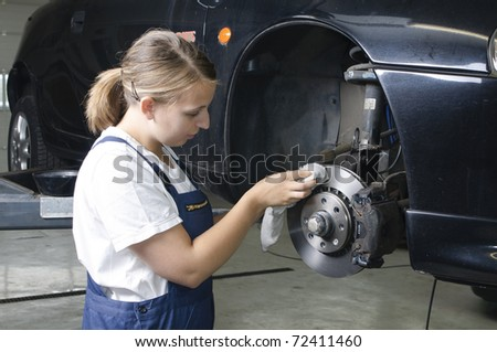 Female car mechanic in a blue overall with the wheel change - stock photo