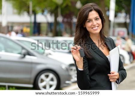 Female car seller holding car keys. Caucasian saleswoman in luxury vehicle trade fair. Auto rental or sales concept. - stock photo