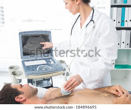 Female cardiologist using sonogram on male patient in examination room - stock photo