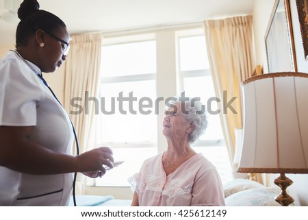 Female care worker nurse assists an elderly female patient with medicines for the day. Home caregiver giving medication dosage to senior woman sitting on bed at home. - stock photo