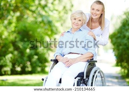 Female caregiver and senior patient in a wheelchair looking at camera outside - stock photo