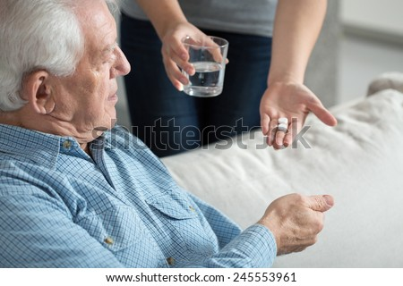 Female caregiver giving the medicine to her older male patient - stock photo