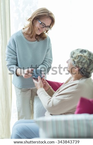 Female carer helping elder woman at home - stock photo