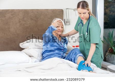 Female caretaker using hot water bag on senior woman's leg in bedroom at nursing home - stock photo