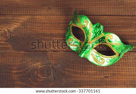 female carnival mask with wooden background - stock photo