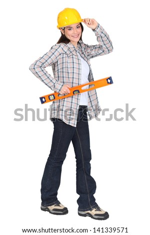 female carpenter holding ruler with hand to hard hat - stock photo