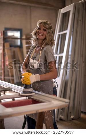 Female carpenter using power sander - stock photo