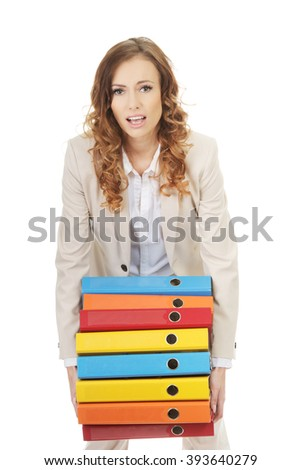 Female carrying heavy binders against. - stock photo